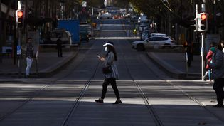Une femme traverse une rue du quartier d'affaires de Melbourne, en Australie, le 17 juin 2020. (WILLIAM WEST / AFP)