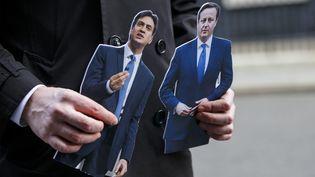Un présentateur de télévision brandit deux figurines à l'effigie d'Ed Miliband (G.) et de David Cameron, le 18 mars 2015, à Londres (Royaume-Uni). (MAXPPP)