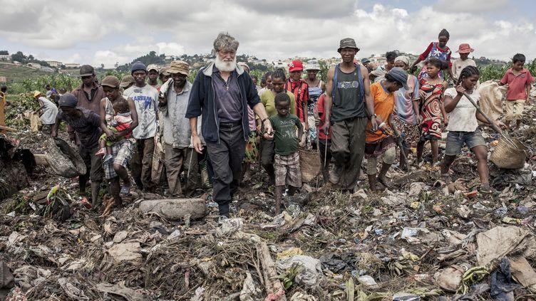Le père Pedro Opeka aux côtés d'habitants d'Antananarivo qui fouillent le dépôt d'ordure de la capitale malgache, le 4 février 2014. (RIJASOLO / AFP)