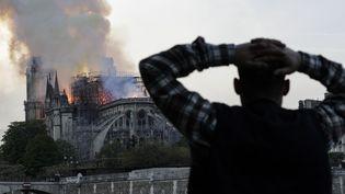 Les passants s'arrêtent, sidérés et impuissants, en voyant le monument le plus visité d'Europe prendre feu. (GEOFFROY VAN DER HASSELT / AFP)
