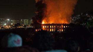 Des Cariocas assistent impuissants à l'incendie qui ravage l'un des monuments de leur ville, le 2 septembre 2018  (STR / AFP)