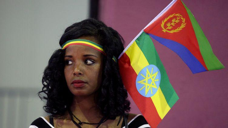 Cette jeune femme arborant les drapeaux éthiopien et érythréen fête à Addis Abeba l'accord de paix signé entre les deux pays en juillet 2018, après vingt ans d'hostilités. (TIKSA NEGERI / X03719)