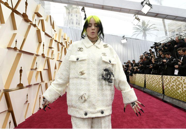 """Billie Eilish a chanté, affublée de son""""pyjama couture""""emblématique dans une veste et un pantalon Chanel blancs agrémentés du fameux logo en double C.Ses cheveux couleur citron vert et ses ongles noirs taillés pour ressembler à des griffes contrastaient avec l'ensemble.92e cérémonie des Oscars, dans la nuit du dimanche 9 au lundi 10 février à Los Angeles. (KEVORK DJANSEZIAN / GETTY IMAGES NORTH AMERICA)"""
