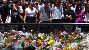 Des passants se recueillent, mardi 16 décembre 2014,devant leparterre de fleurs déposées devant un café de Sydney (Australie), en hommage aux victimes de la prise d'otages qui s'y est déroulée la veille. (DAVID GRAY / REUTERS)