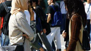 Une lycéenne porte le voile devant son établissement scolaire (image d'illustration). (FREDERICK FLORIN / AFP)