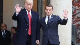 Donald Trump et Emmanuel Macron saluent les photographes, le 10 novebre 2018, sur le perron de l'Elysée, à Paris. (LUDOVIC MARIN / AFP)