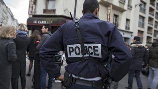 Un policier devant des restaurants et des cafés visés par des attaques, trois jours après l'assaut des terroristes, le 16 novembre, à Paris. (ETIENNE LAURENT / EPA / MAXPPP)