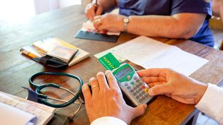 Un médecin pratique la télétransmission avec la carte vitale de son patient en Dordogne, le 7 juin 2012. (BURGER / PHANIE / AFP)