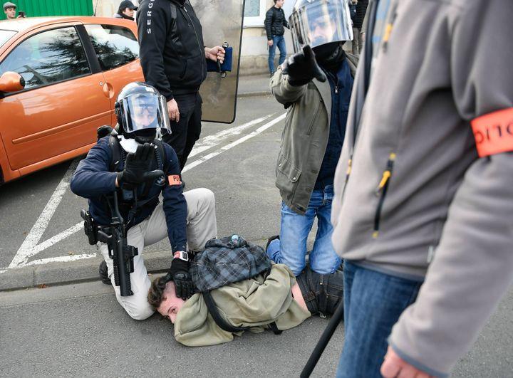 Le policier à droite a lâché son LBD, qui pend à nouveau, mais plus loin du crâne de l'homme qu'il continue de maintenir au sol. (MAXPPP)