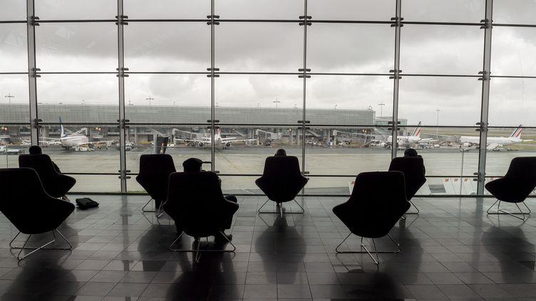 Des passagers sont assis dans des sièges du terminal 2E de l'aéroport Roissy-Charles de Gaulle, près de Paris, le 18 mars 2021. (ERIC PIERMONT / AFP)