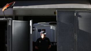 Mardi 6 août 2013, un policier monte la garde, à Madrid (Espagne), devant un van censé transporter Daniel Galvan, un resortissant espagnol condamné au Maroc pour pédophilie et gracié par erreur. (JUAN MEDINA / REUTERS )