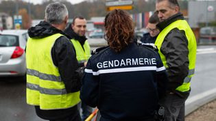 """Un gendarme vérifie les identités de """"gilets jaunes"""" à Pont-de-Beauvoisin, en Savoie, où une automobiliste a mortellement fauché une manifestante samedi 17 novembre. (ROMAIN LAFABREGUE / AFP)"""