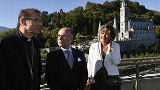 L'évêque de Tarbes et Lourdes, Monseigneur Brouwet (à gauche), Bernard Cazeneuve (au centre) et la maire de Lourdes, Josette Bourdou (à droite), le 13 août 2016 à Lourdes (Hautes-Pyrénées). (PASCAL PAVANI / AFP)