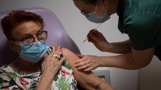 Une pharmacienne administre une dose du vaccin d'AstraZeneca à une femme à Savenay (Loire-Atlantique), le 2 avril 2021. (LOIC VENANCE / AFP)