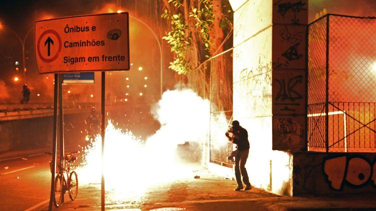 Un cocktail Molotov éclate dans une rue de Rio (Brésil), le 22 juillet 2013, lors d'une manifestation contre le coût de la visite du pape et des JMJ. (TASSO MARCELO / AFP)