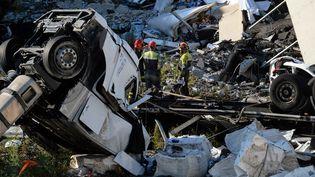 Les sauveteurs cherchent des survivants dans les décombres du pont de Gênes (Italie), le 14 août 2018. (ANDREA  LEONI / AFP)