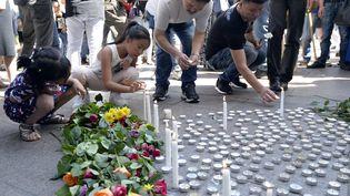 Des gens allument des bougies à Aubervilliers (Seine-Saint-Denis), le 14 août 2016, pour rendre hommage à Zhang Chaolin, un cuisinier Chinois assassiné dans la commune. (ALAIN JOCARD / AFP)