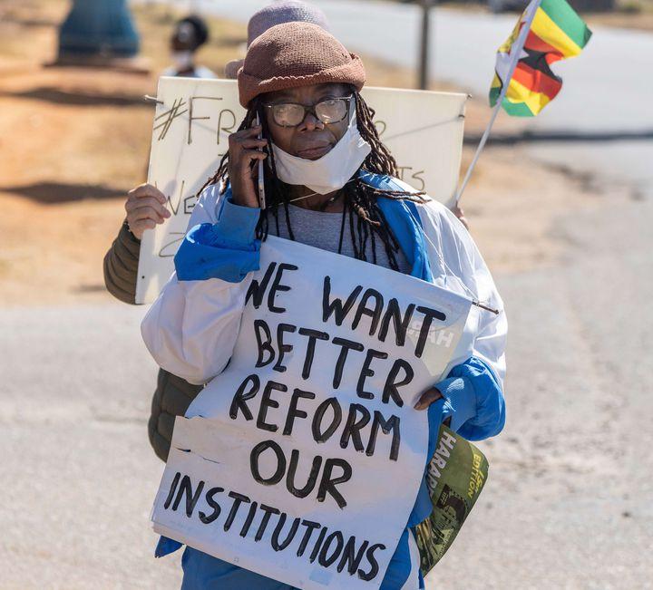 """L'écrivaine zimbabwéenneTsitsi Dangarembga le 31 juillet 2020 à Harare, à la manifestation durant laquelle elle a été arrêtée. Sur la pancarte qu'elle tient, on peut lire : """"Nous voulons une meilleure réforme"""" et """"nos institutions"""". (ZINYANGE AUNTONY / AFP)"""