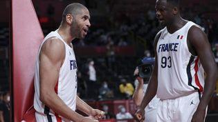 Nicolas Batum (à gauche) et Moustapha Fall (à droite) célèbrent la victoire de la France sur la Slovénie en demi-finale du tournoi olympique de basket, le 5 août 2021. (THOMAS COEX / AFP)