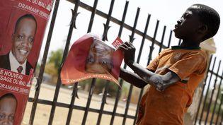 Un garçon colle des affiches électorales à Gao, au Mali, le 25 juillet 2013. (KENZO TRIBOUILLARD / AFP)