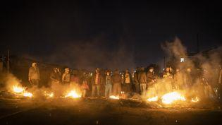 Des habitants armés rassemblés à un barrage routier pour empêcher les pillages dans le canton de Phoenix au nord de Durban (15 juillet 2021). (GUILLEM SARTORIO / AFP)