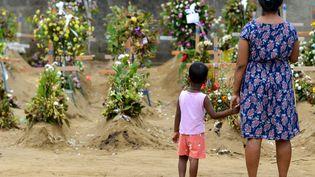Une mère et son enfant se recueillent devant les tombes de victimes des attentats qui ont visé des églises à Negombo (Sri Lanka), le 28 avril 2019. (ISHARA S. KODIKARA / AFP)