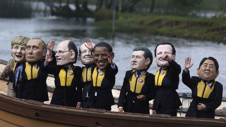 """Des manifestants portant les """"grosses têtes"""" des dirigeants du G8 manifestent contre la faim à l'occasion du sommet du G8 sur le lac d'Enniskillen (Irlande du Nord), le 17 juin 2013. (LEFTERIS PITARAKIS / AP / SIPA)"""