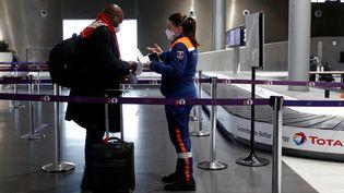 Un passager est contrôlé à l'aéroport Roissy-Charles de Gaulle, le 5 février 2021. (GONZALO FUENTES / POOL / AFP)