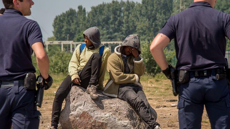 Deux policiers à proximité de migrants, à Calais (Pas-de-Calais), le 1er juin 2017. (PHILIPPE HUGUEN / AFP)