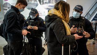 Des policiers contrôlent des attestations de déplacement, le 27 mars 2021, à Lyon. (NICOLAS LIPONNE / HANS LUCAS / AFP)