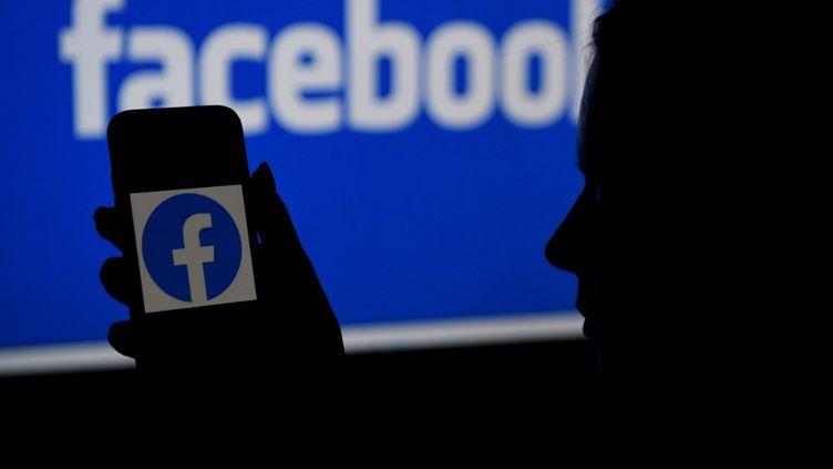 Une personne tenant un téléphone avec le logo de Facebook, à Arlington (Virginie, Etats-Unis), le 7 avril 2021. (OLIVIER DOULIERY / AFP)