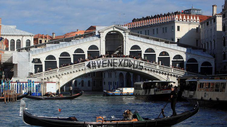 Une banderole dénonçant l'exode forcé des Vénitiens face au tourisme de masse, déployée sur le pont du Rialto, le 12 novembre 2016, à Venise (Italie). (MANUEL SILVESTRI / REUTERS)