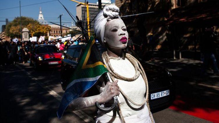 Une femme vêtue d'une robe de mariée tient un drapeau sud-africain lors d'une marche organisée le 20 mai 2017 à Pretoria contre les violences faites aux femmes. (WIKUS DE WET / AFP)