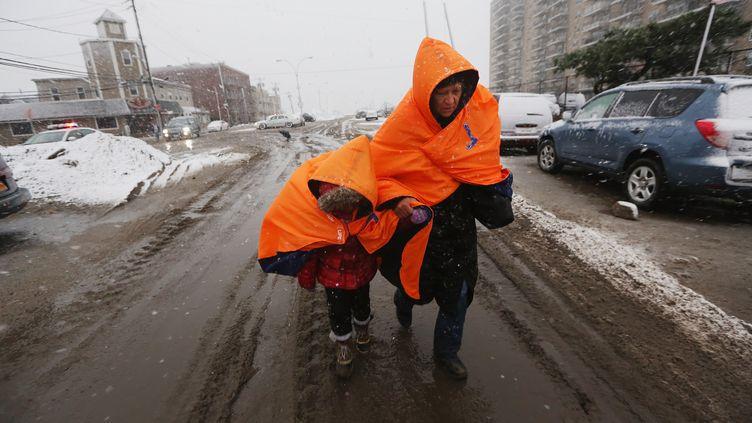 Une femme et sa fille, sinistrées après le passage du cyclone Sandy, traversent un carrefour du Queens à New York (Etats-Unis), le 7 novembre 2012, pendant une tempête de neige. (MARIO TAMA / GETTY IMAGES NORTH AMERICA / AFP)