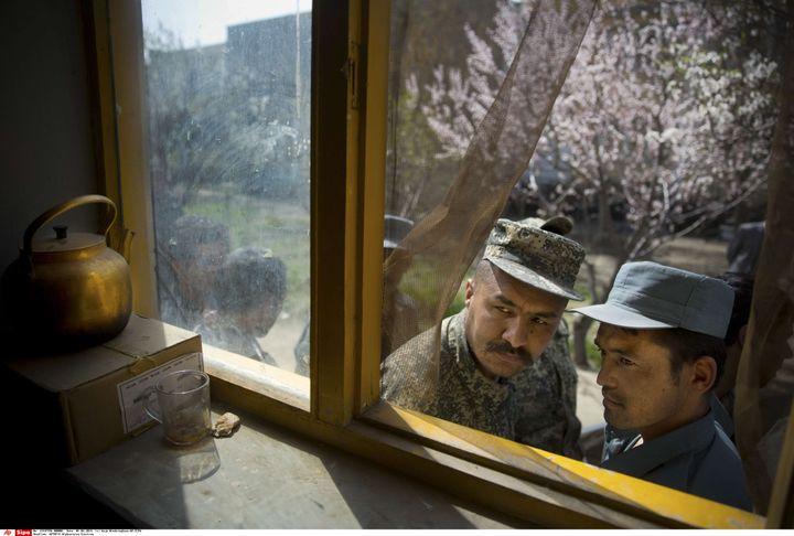 Un soldat afghan (à gauche) et un policier font le queue pour obtenir leurs cartes d'électeur, à Kaboul (Afghanistan), le 1er avril 2014. (ANJA NIEDRINGHAUS / AP / SIPA)