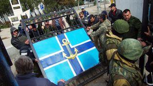 Des miliciens pro-russes démontent le portaildu siège de la marine à Sébastopol, en Crimée, avant de prendre possession des lieux, mercredi 19 mars 2014. (VASILIY BATANOV / AFP)