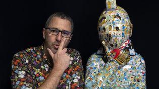 """Le plasticien Christophe Tixier, alias """"Peppone"""", pose avec une sculpture de Tintin, le 13 avril 2021 (CHRISTOPHE SIMON / AFP)"""