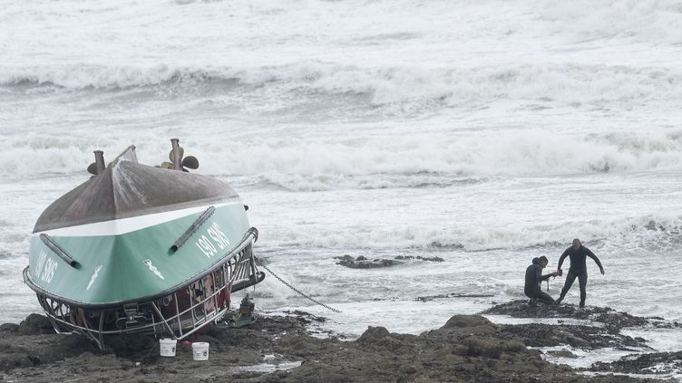 Des officiers amarrent l'épave de la vedette de la SNSM le 7 juin 2019 sur une plage des Sables d'Olonne. (SEBASTIEN SALOM-GOMIS / AFP)