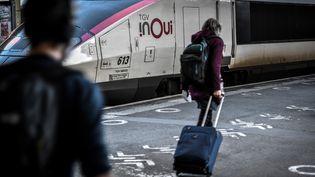 Une voyageuse dans le hall de départ de la Gare de Lyon à Paris, le 18 décembre 2020,. (STEPHANE DE SAKUTIN / AFP)