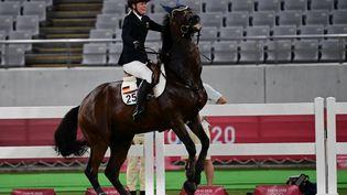 L'Allemande Annika Schleu se débat face à son cheval, tiré au sort, qui refuse l'épreuve de saut d'obstacles, le 6 août 2021. (PEDRO PARDO / AFP)