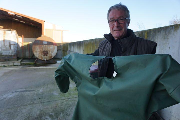 Dominique Marchal montre la combinaison que doit porter son salarié avant d'épandre les produits, le 29 janvier 2016, près du local àpesticides de son exploitation de Serres (Meurthe-et-Moselle). (JULIE RASPLUS / FRANCETV INFO)