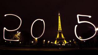 Un touriste écrit 2015 avec un stylo lumineux devant la Tour Eiffel à Paris le 30 décembre 2014. (CHEN XIAOWEI / XINHUA)