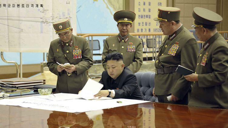 Cette photo a été diffusée par l'agence officielle nord-coréenne (KCNA), le 29 mars 2013. Le dirigeant Kim Jong-un consulte des documents, avec en arrière-plan une carte d'opérations militaires. (KNS / KCNA / AFP)