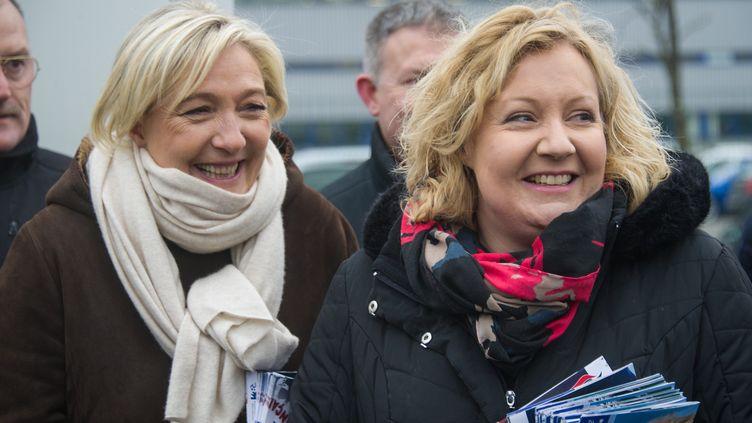 Marine Le Pen et Sophie Montel,candidate FN à la législative partielle dans le Doubs, distribuent des tracts devant l'entreprise PSA Peugeot Citroën le 23 janvier 2015 à Montbéliard. (SEBASTIEN BOZON / AFP)