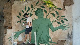 """L'artiste grec Fikos, qui se décrit comme un """"néo-muraliste"""", travaille sur l'une de ses peintures murales dans la capitale chypriote Nicosie le 4 juin 2021. (DAVID VUJANOVIC / AFP)"""