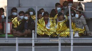 Des migrants pourvus de couverture de survie arrive sur un bâteau de la police douanière et financière italienne le 17 mai 2021 pour débarquer sur l'île de Lampedusa au Sud de l'Italie.   (ALBERTO PIZZOLI / AFP)