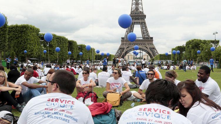Des jeunes engagésdans le service civique, sur la pelouse du Champs-de-Mars, près de la tour Eiffel à Paris, le 27 juin 2012. (JACQUES DEMARTHON / AFP)