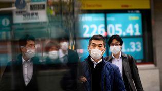 Des passants portent des masques pour se protéger du coronavirus, mardi 25 février 2020. (PHILIP FONG / AFP)
