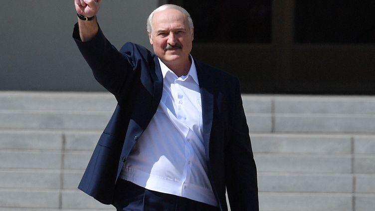 Le président Alexandre Loukachenko lève son poing en arrivant à un meeting à Minsk, en Biélorussie, le 16 août 2020. (VIKTOR TOLOCHKO / SPUTNIK / AFP)