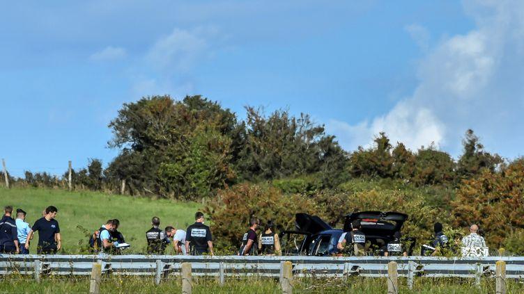 Des policiers inspectentle véhicule BMW du suspect après son interpellation, mercredi 9 août 2017 sur l'autoroute A16, près de Marquise (Pas-de-Calais). (PHILIPPE HUGUEN / AFP)